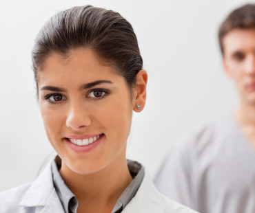Portrait of smiling female doctor with practitioner standing in background